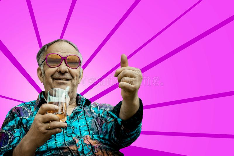 Grandpa shows thumb up on pink background stock photo