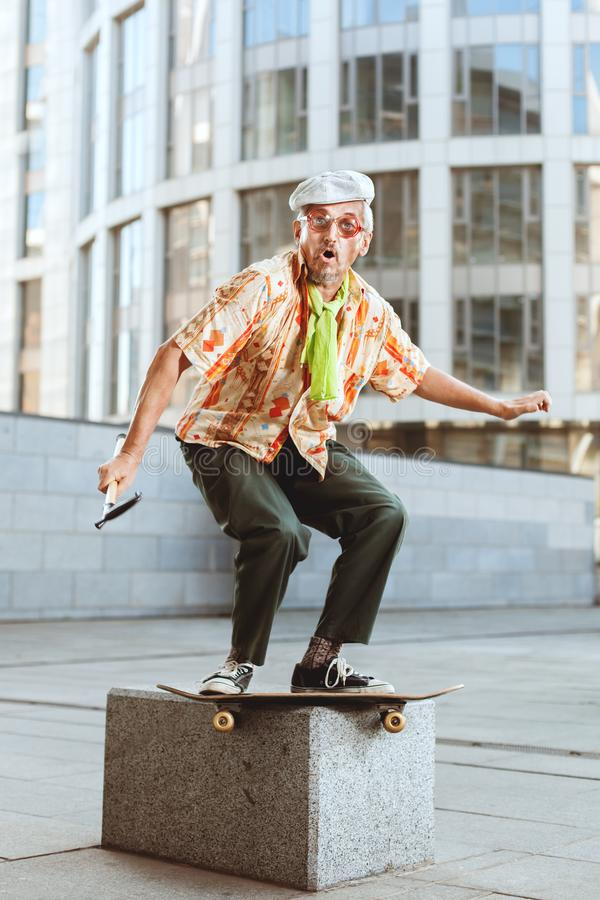 Grandpa on a skateboard is jumping. royalty free stock image