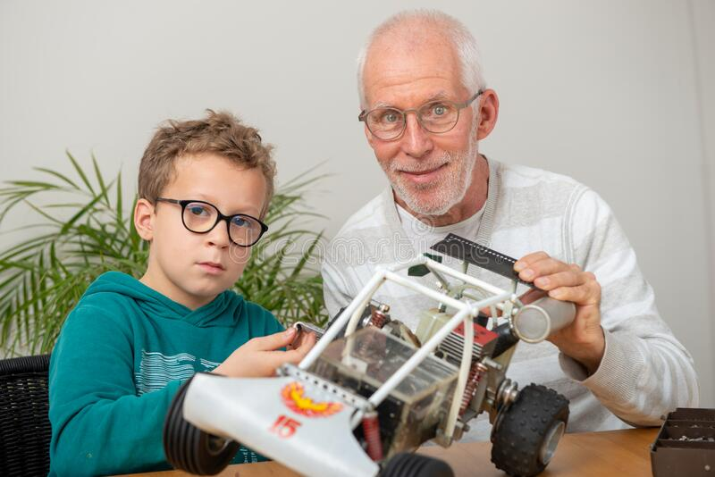 Grandpa and son little boy repairing  model radio-controlled car. At home stock photo