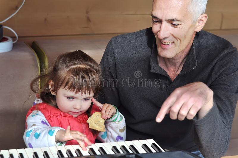 Grandpa teaches little girl to play piano. Concept of music study and creative hobby stock photography