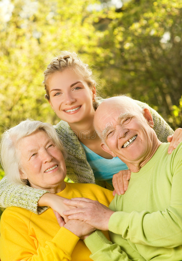 Grandparants with granddaughter outdoors stock photo