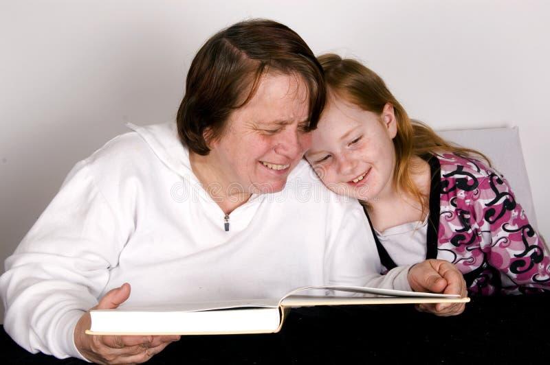 Grandparent is reading to grandchild. Grandparent is reading a happy book to her grandchild stock photos