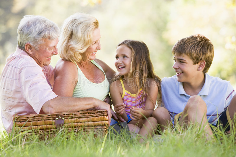 grandparents внучат имея пикник стоковые изображения rf