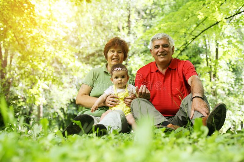 Grandparents with baby girl in the park. royalty free stock images