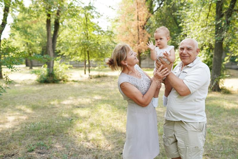 Grandparents and baby grandchild walking in nature park, copy space.  royalty free stock images