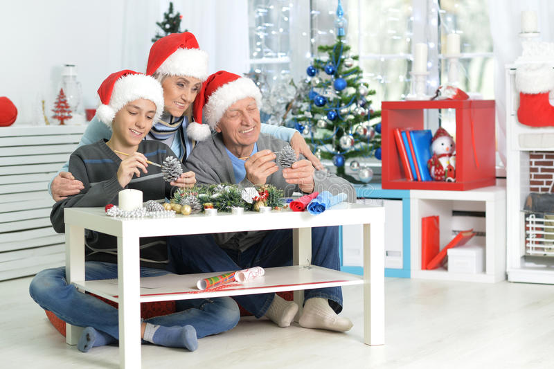 Grandparents with boy preparing for Christmas. Happy grandparents with their teen grandson preparing for Christmas at home royalty free stock image
