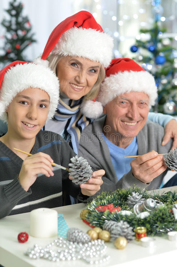 Grandparents with boy preparing for Christmas. Happy grandparents with their teen grandson preparing for Christmas at home stock image