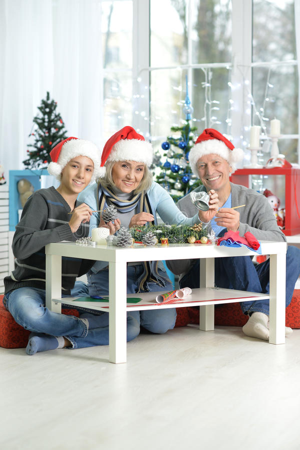 Grandparents with boy preparing for Christmas. Happy grandparents with their teen grandson preparing for at home royalty free stock image