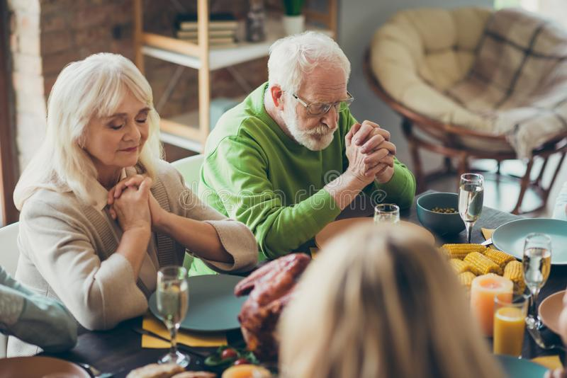 Grandparents charming couple gathering sit table celebrate thanksgiving day pray with family relatives have banquet in stock photo