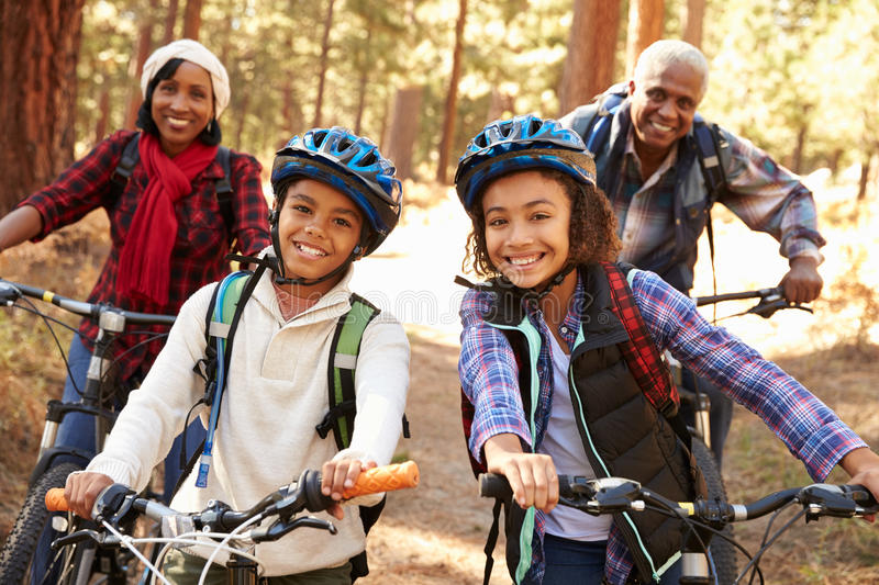 Grandparents With Children Cycling Through Fall Woodland royalty free stock photography
