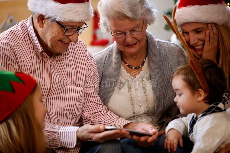 Grandparents with children looking Christmas photos on cell phone. Happy grandparents with children looking Christmas photos on cell phone royalty free stock image