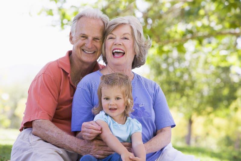 Grandparents com a neta no parque imagens de stock royalty free