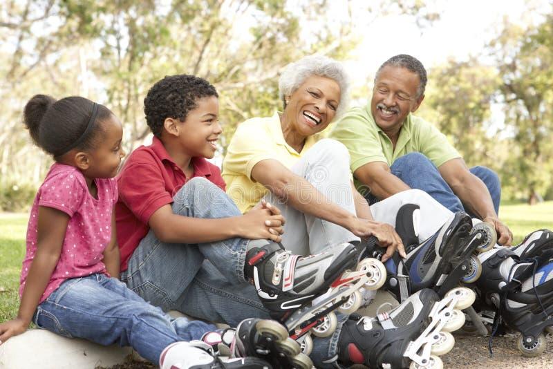 Grandparents com os netos que põr sobre patins imagens de stock royalty free