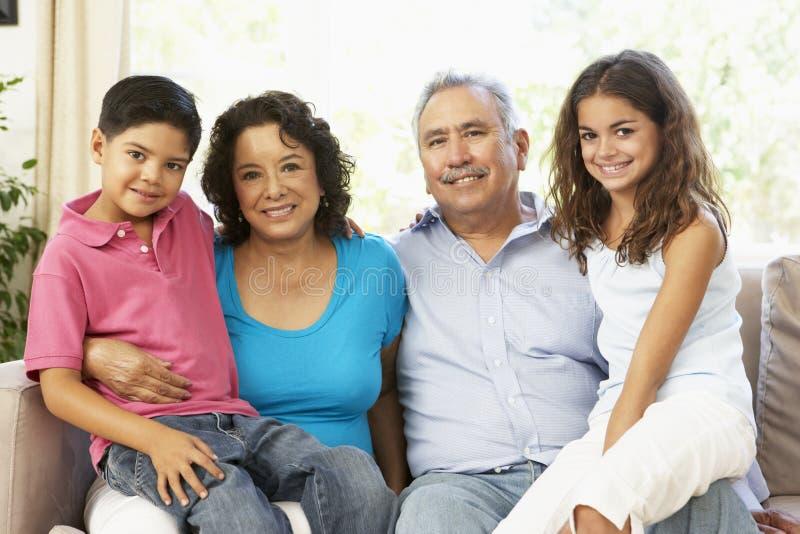 Grandparents com os netos que relaxam em casa T foto de stock royalty free