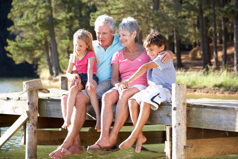 Grandparents com os netos que sentam-se por um lago fotos de stock royalty free