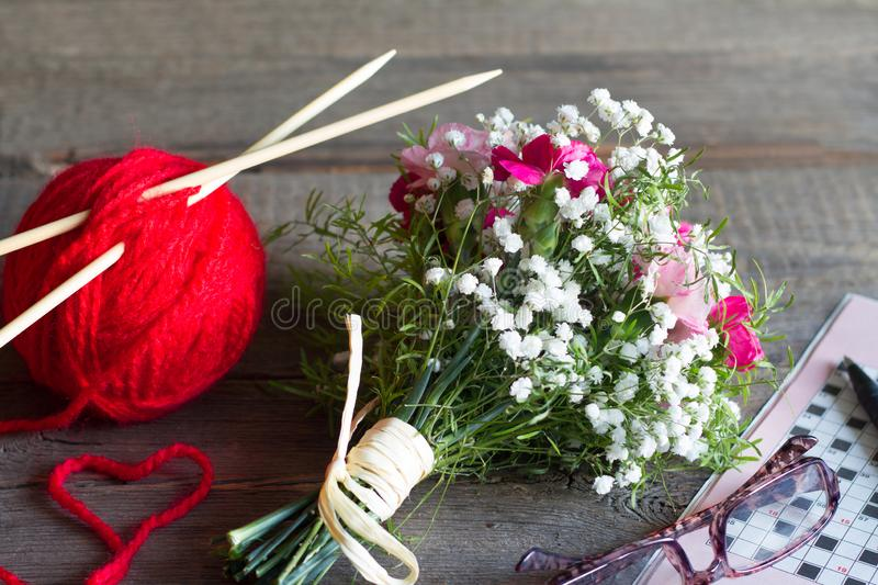 Grandparents day abstract concept with knitting crossword and bouquet of flowers. Closeup royalty free stock photos