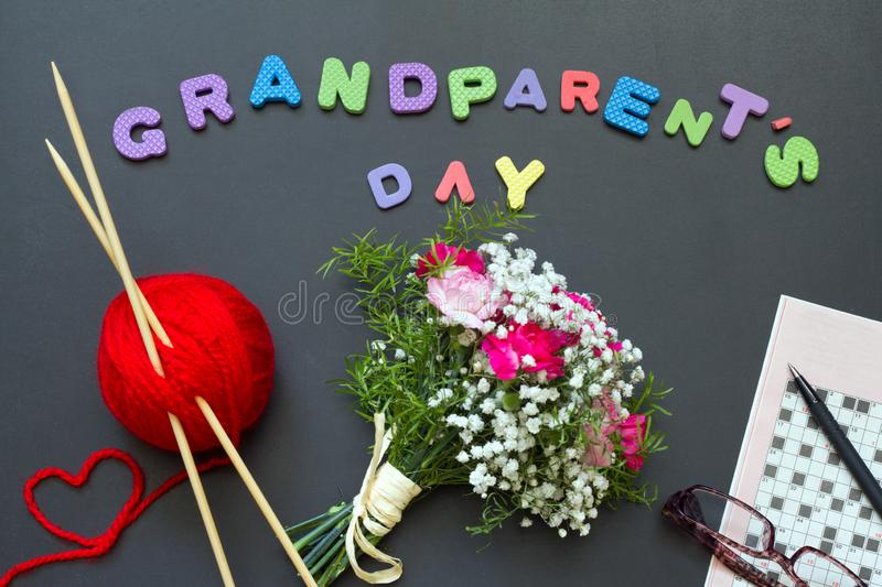 Grandparents day abstract concept with knitting crossword and bouquet of flowers. Closeup stock photo
