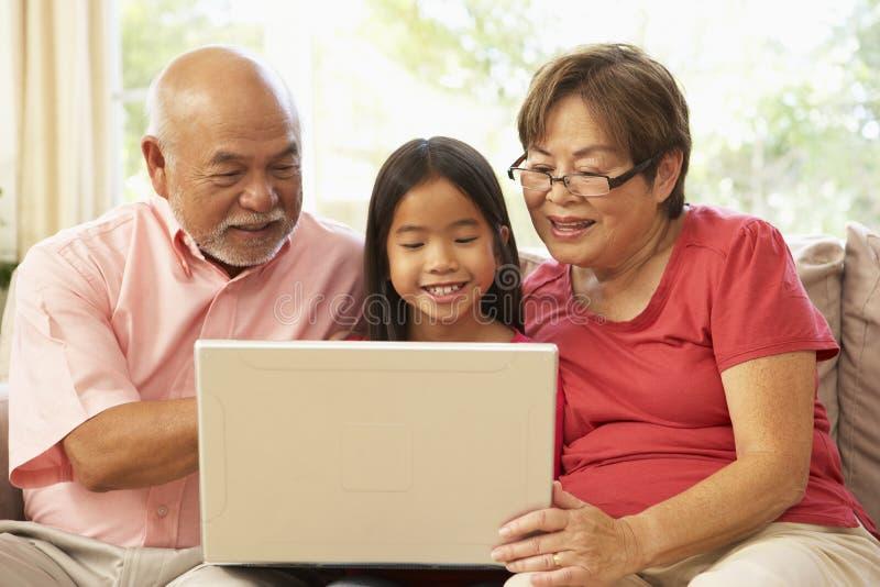 Grandparents e Grandaughter usando o cálculo do portátil fotografia de stock