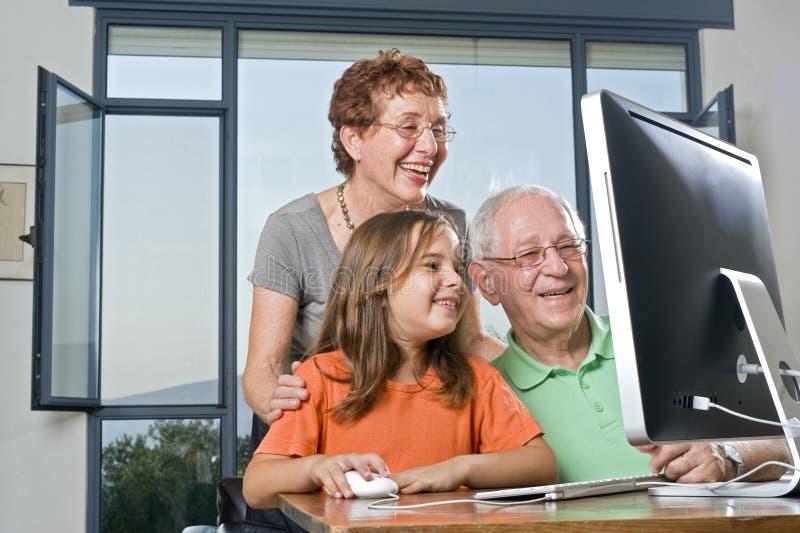Grandparents e neta com computador fotografia de stock royalty free