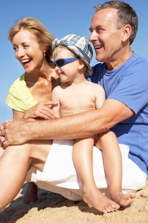 Grandparents e neto que sentam-se na praia imagem de stock