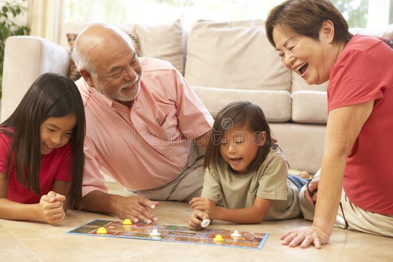 Grandparents e netos que jogam o jogo de mesa imagens de stock