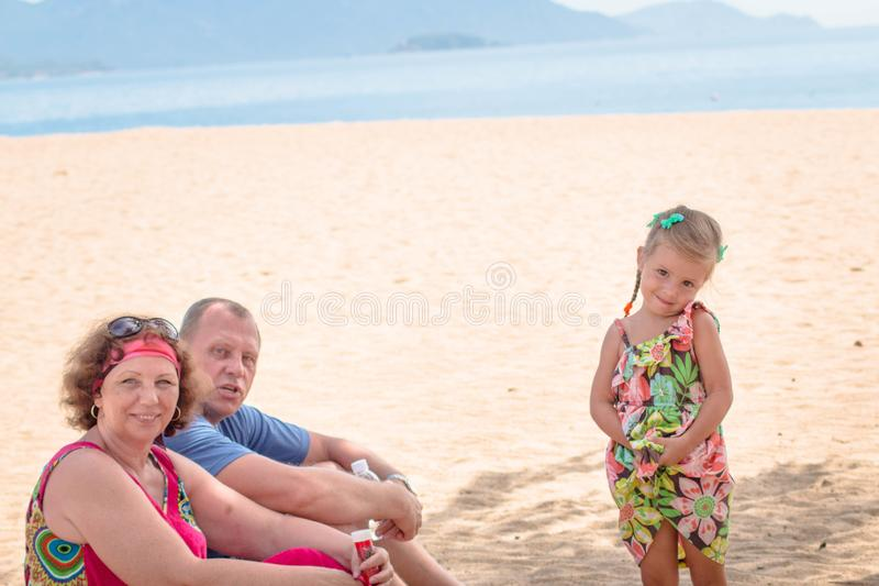 Grandparents enjoying day with granddaughter while blowing soap bubbles on the beach near the sea.  stock photo