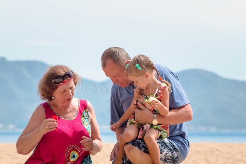 Grandparents enjoying day with granddaughter while blowing soap bubbles on the beach near the sea.  royalty free stock photos