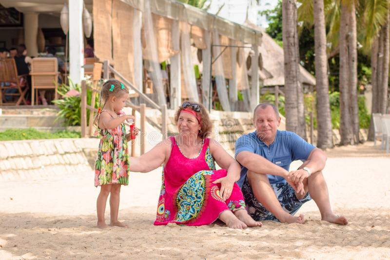 Grandparents enjoying day with granddaughter while blowing soap bubbles on the beach near the sea.  stock photography