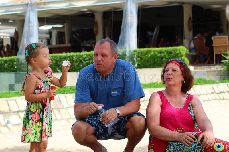 Grandparents enjoying day with granddaughter while blowing soap bubbles on the beach near the sea.  stock image
