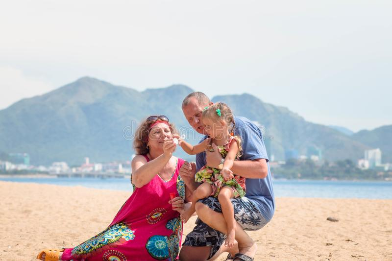 Grandparents enjoying day with granddaughter while blowing soap bubbles on the beach near the sea.  royalty free stock images