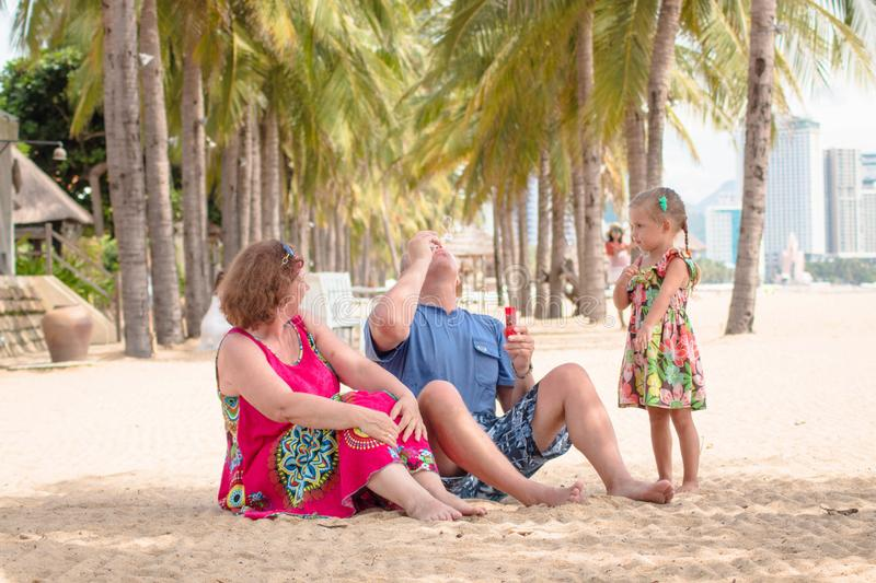 Grandparents enjoying day with granddaughter while blowing soap bubbles on the beach near the sea.  royalty free stock photography