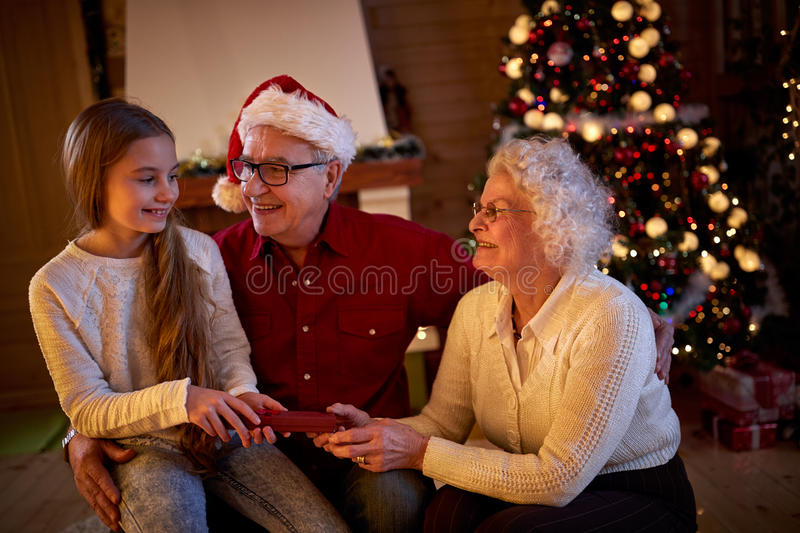 Grandparents giving gifts granddaughter at Christmas eve. Happy grandparents giving gifts granddaughter at Christmas eve stock images