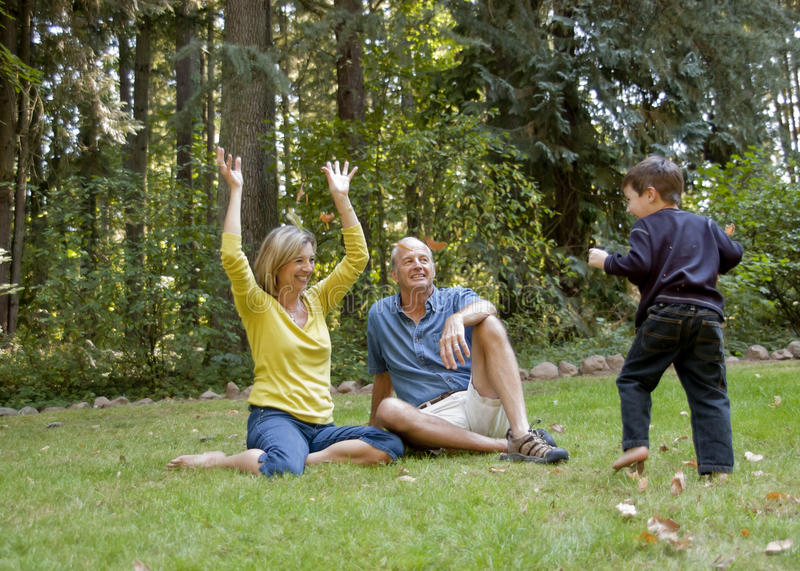 Grandparents and grandchild playing with leaves. Older couple play with leaves with their grandchild stock photos