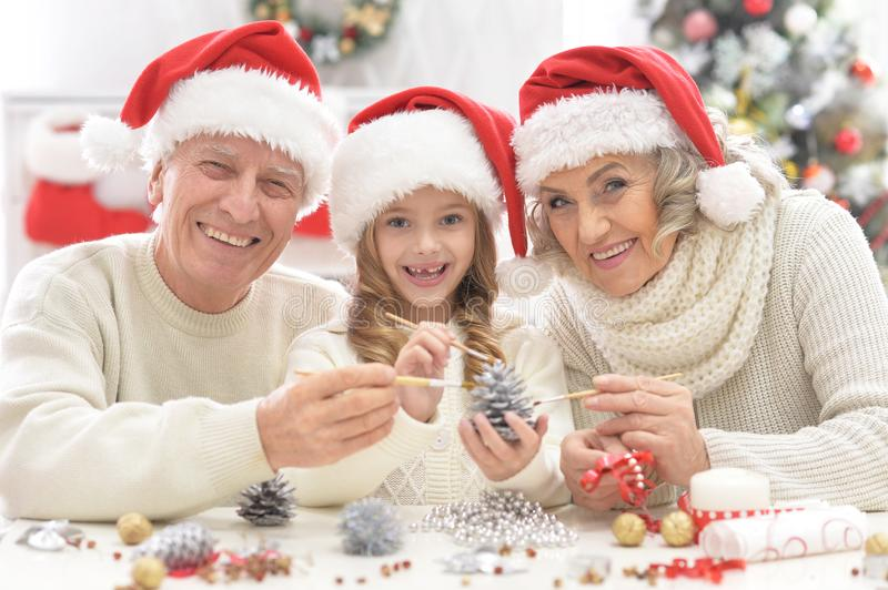 Grandparents with grandchild preparing for Christmas royalty free stock photos