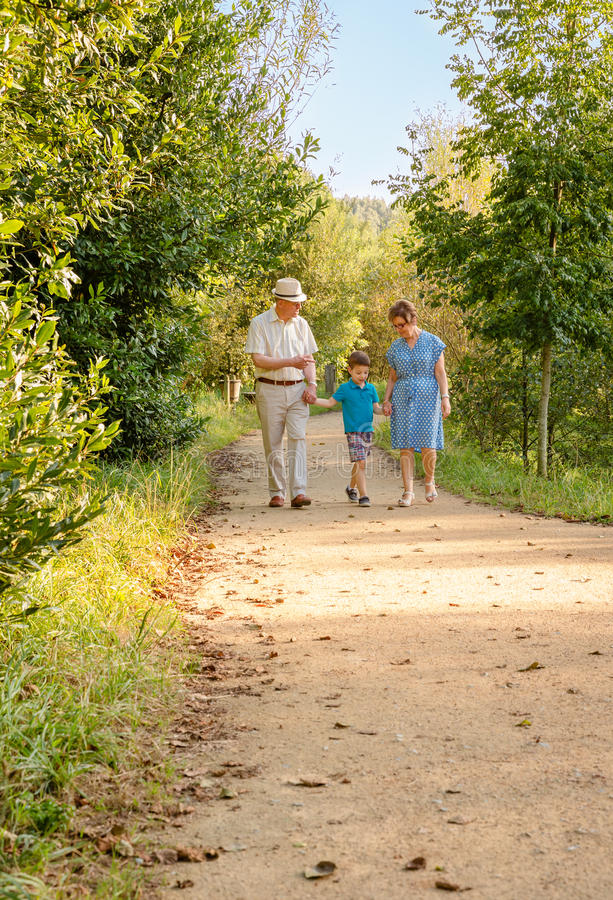 Grandparents and grandchild walking outdoors royalty free stock images