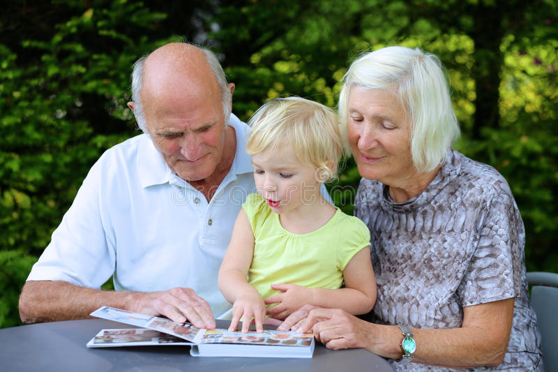 Grandparents with grandchild watching photo album. Happy smiling grandparents relaxing outdoors in the garden watching with their granddaughter photo book, a royalty free stock photo