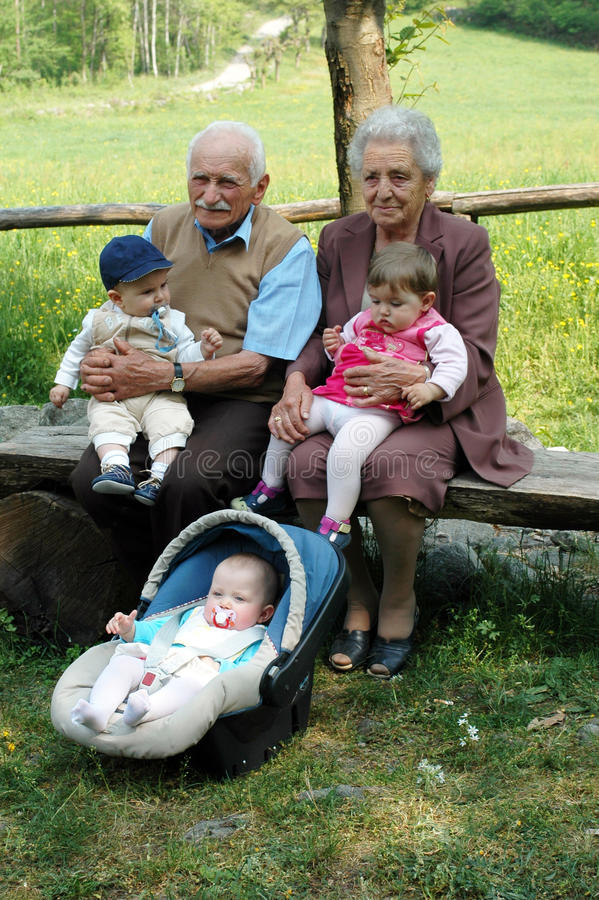 Grandparents with grandchildren. Grandparents with three grandchildren sitting on a bench in a park during a family reunion stock image