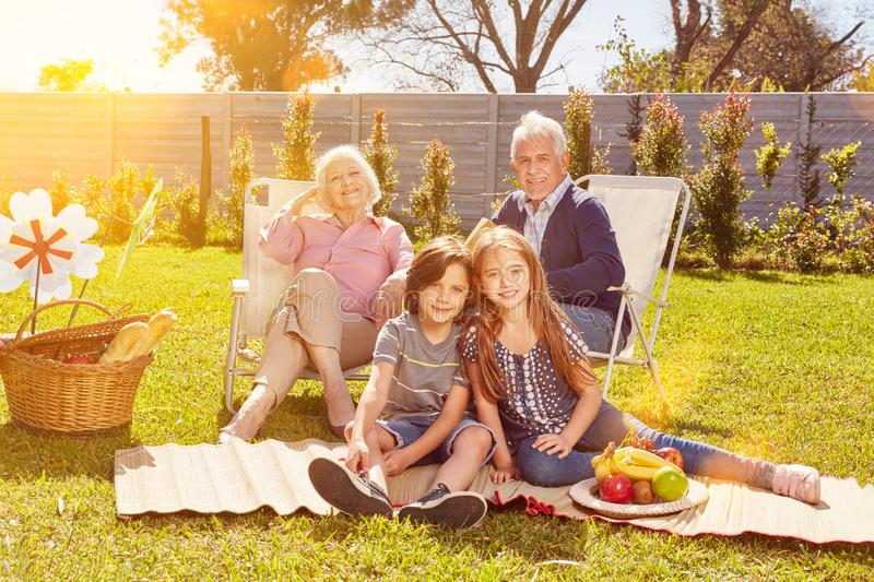 Grandparents and grandchildren as a family at a picnic. Grandparents and grandchildren as a family having a picnic in the garden in summer stock photo