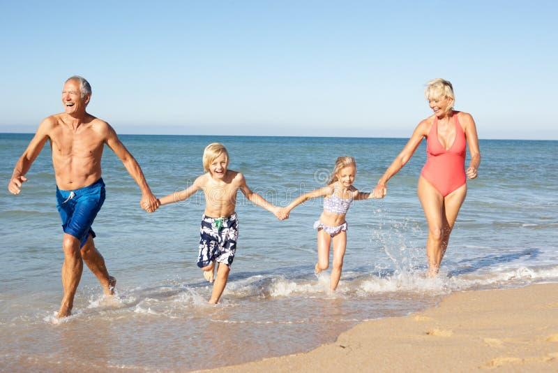 Grandparents With Grandchildren On Beach. stock photography