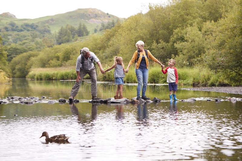 Grandparents With Grandchildren Crossing River Whilst Hiking In UK Lake District stock image