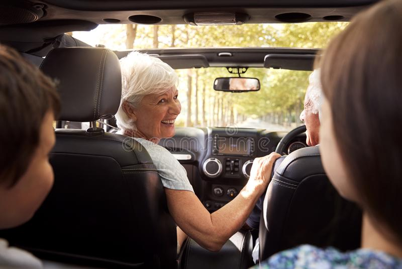 Grandparents And Grandchildren Driving In Open Top Car royalty free stock photos