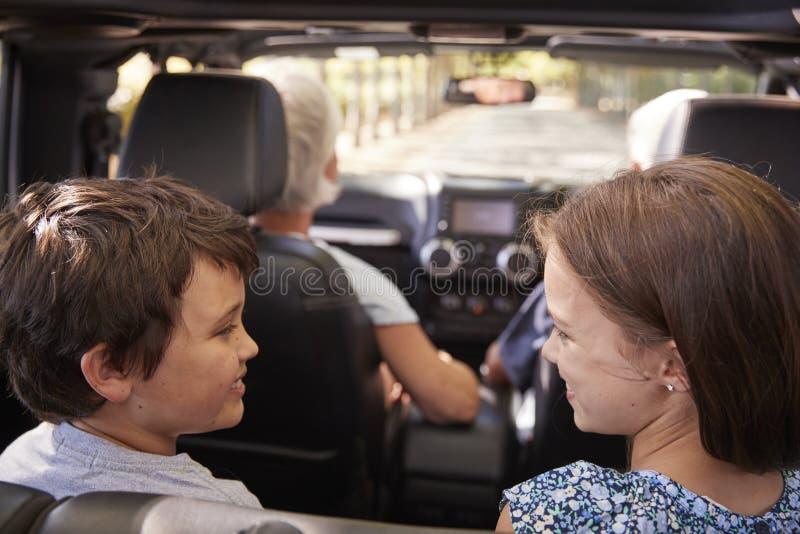 Grandparents And Grandchildren Driving In Open Top Car stock image