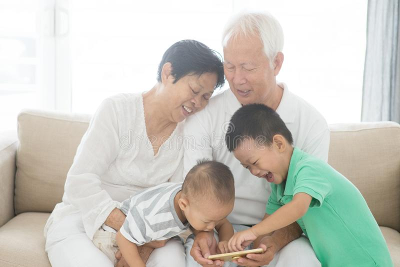 Grandparents and grandchildren using smart phones stock photo