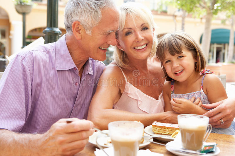 Grandparents With Granddaughter in cafe stock photos