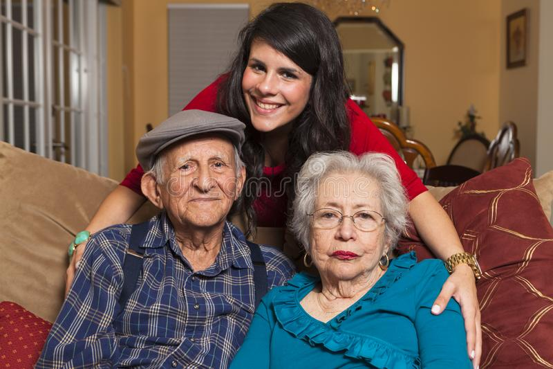 Grandparents and Granddaughter. Elderly 80 plus year old grandparents with granddaughter in a home setting stock photos