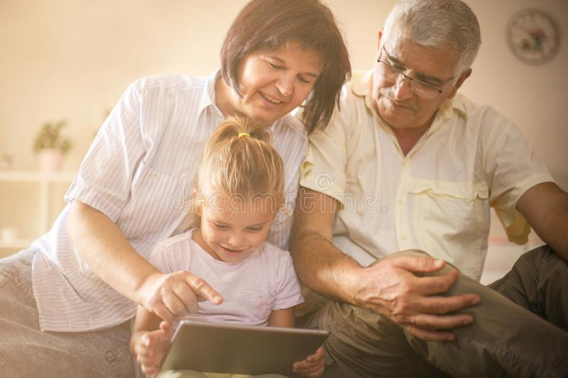 Grandparents with granddaughter at home. stock images