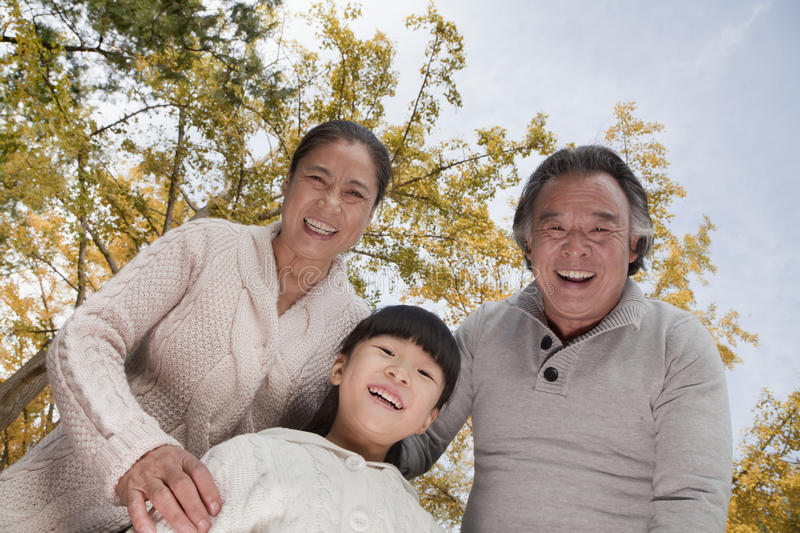 Grandparents and granddaughter smiling and looking down in park royalty free stock images