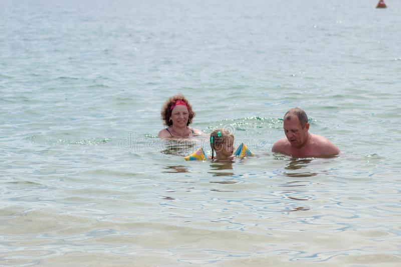 Grandparents And Granddaughter swimming in the sea, they smile and happyness.  stock photos