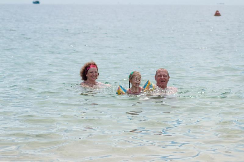 Grandparents And Granddaughter swimming in the sea, they smile and happyness.  stock image
