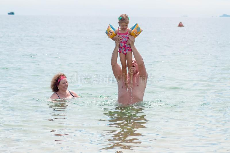 Grandparents And Granddaughter swimming in the sea, they smile and happyness.  royalty free stock image